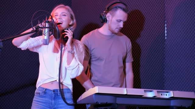 vídeos de stock e filmes b-roll de dual singer at music sound recording studio - audio available