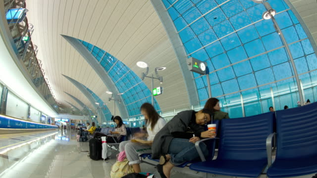 T/L WS Dubai Airport at dawn with sleepy travelers waiting in foreground/ Dubai, United Arab Emirates