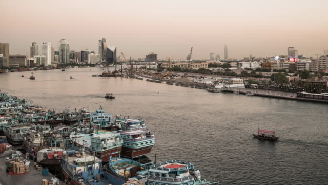 dubai creek at dusk with passing cargo boats - day to dusk stock videos & royalty-free footage