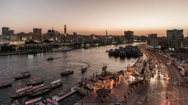 Dubai Creek at sunset with passing traffic and boats