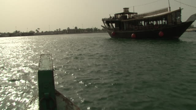 dubai creek. traveling view from a boat of a dhow and an abra or water taxi. the creek divides dubai into two main areas, deira and bur dubai. - ダウ船点の映像素材/bロール