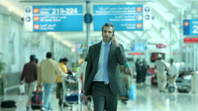 dubai international airport. view of a passenger, a businessman, in a suit on his mobile phone inside a terminal building at the airport. - businessman stock videos & royalty-free footage