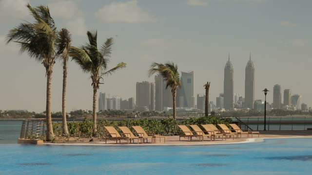 dubai media city. view from palm island across an infinity pool to the gulf sea and the skyline of dubai media city. - infinity pool stock videos & royalty-free footage