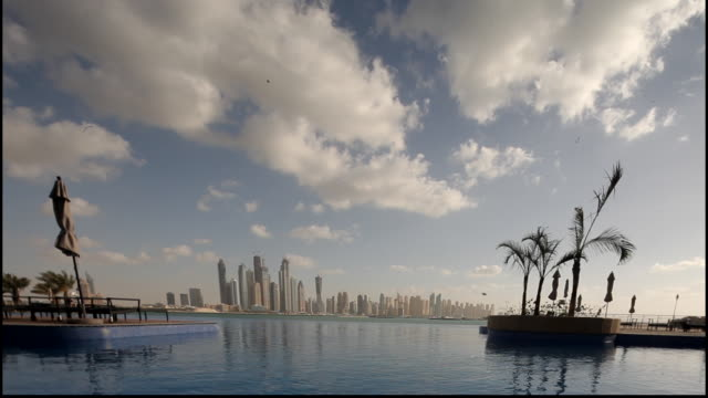 dubai skyline. view across an infinity pool in a resort to the skyline of dubai in the distance across the gulf sea. - infinity pool stock videos & royalty-free footage