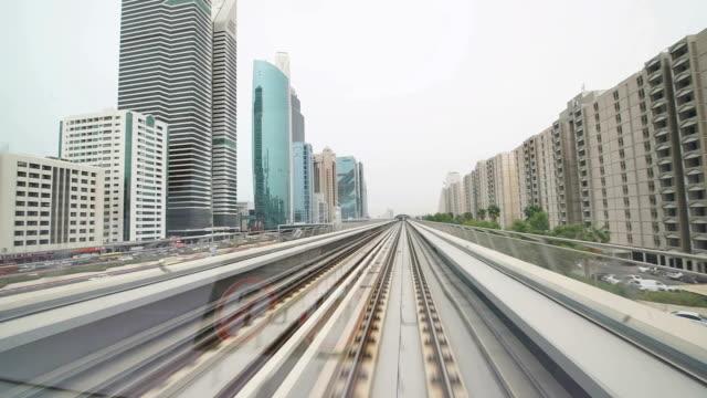 pov dubai metro fährt entlang der wolkenkratzer - einschienenbahn stock-videos und b-roll-filmmaterial