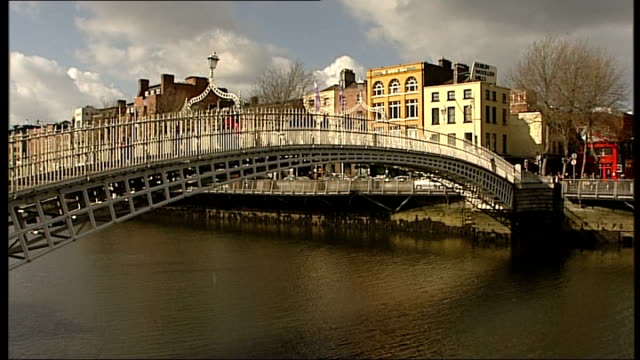 dublin city views river liffey under grey sky / dublin city flag on lamppost / more street scenes / general views ha'penny bridge and people crossing... - plucking an instrument stock videos and b-roll footage