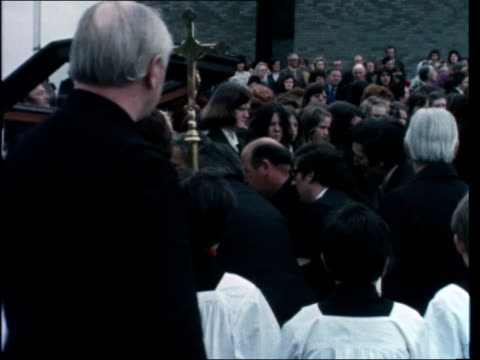 dublin funerals; ireland: dublin: clergy lead cortege zoom in to coffin of maureen shields - put into hearse - sof bell tolls from church: mourners:... - トレバー マクドナルド点の映像素材/bロール