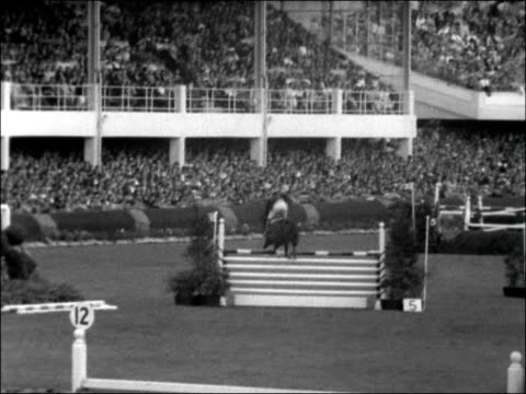 Dublin Horse Show 1956 REPUBLIC OF IRELAND Dublin EXT Shots of horses paraded at show / Men in stands / Horse taking part in show jumping event /...