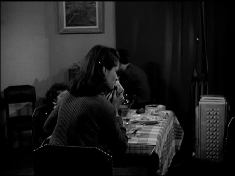 vídeos de stock e filmes b-roll de paris france dramatization 'dubois family' finishing meal 'andre' having cigarette reading paper by radio while 'suzanne' leaves room w/ 'michele'... - 1947