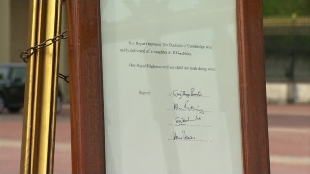 Duchess of Cambridge gives birth to girl Buckingham Palace Footmen along with birth announcement document and putting it on easel Close Shot of...