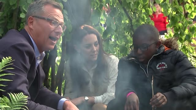 duchess of cambridge visits chelsea flower show; england: london: chelsea: various of duchess of cambridge and children sat around bonfire - festival dei fiori di chelsea video stock e b–roll