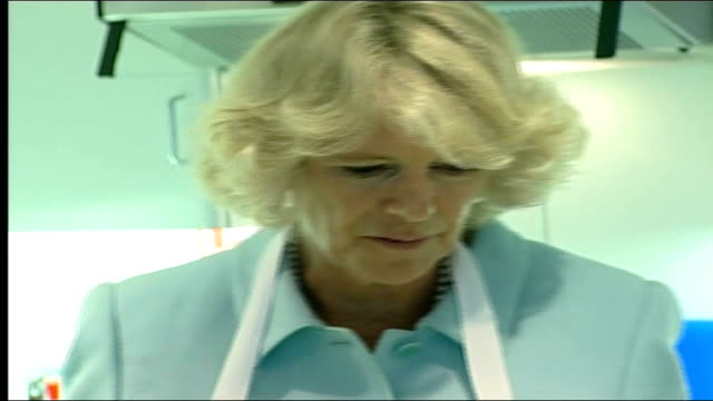 vidéos et rushes de duchess of cornwall visit to school in crewe camilla in kitchen area of bus where children are preparing food and along to table with teacher and... - enseignante