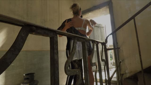 due ballerini ridono dopo che una porta si chiude davanti a loro per un colpo di vento - vento stock videos & royalty-free footage