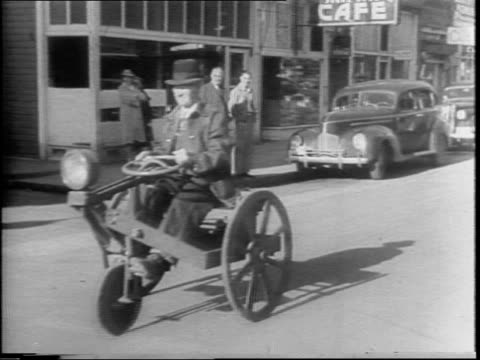 due to gas rationing mr scammerhorn builds an adult size tricycle invention / closeup of the bike / he rides it up and down the main street parallel... - anno 1942 video stock e b–roll