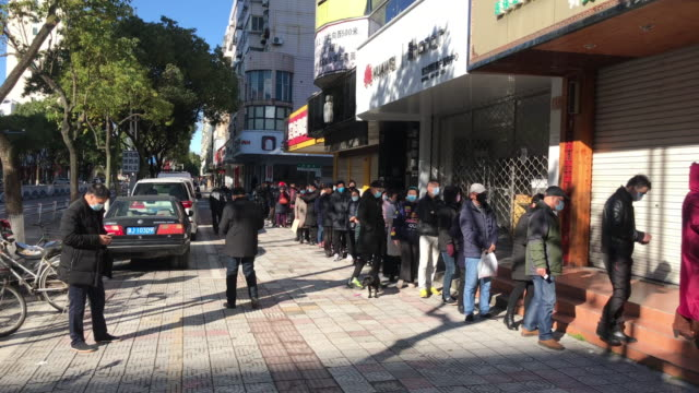 due to the serious epidemic situation people in zhejiang wearing face masks are queuing up to buy masks with limited distribution a total of 2762... - wuhan stock-videos und b-roll-filmmaterial
