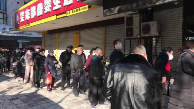 due to the serious epidemic situation people in zhejiang wearing face masks are queuing up to buy masks with limited distribution a total of 2762... - coronavirus stock videos & royalty-free footage