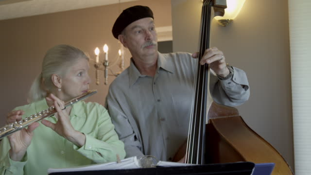 A duet laughs and interrupts their performance as they practice at home.