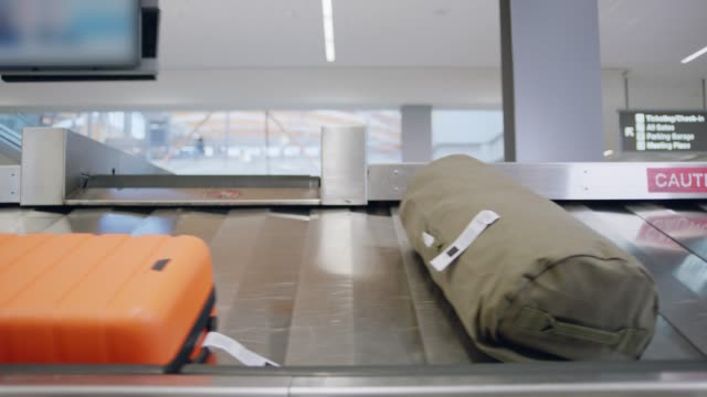 vídeos de stock, filmes e b-roll de duffel bag slides onto conveyor belt among other suitcases in airport baggage claim. - locais geográficos