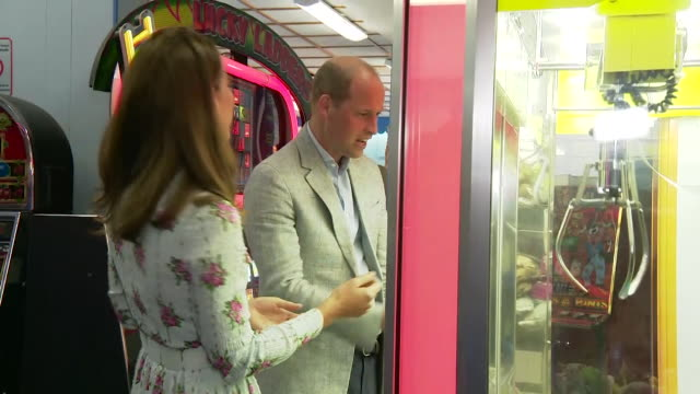 duke and duchess of cambridge have a go at grab a teddy claw machine in arcade on barry island wales - leisure games stock videos & royalty-free footage