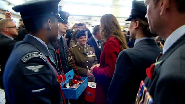 vídeos de stock e filmes b-roll de duke and duchess of cambridge join poppy appeal william and kate chatting with poppy sellers in station / kate looking at remembrance wristband... - pulseira