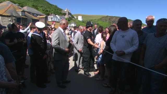 duke and duchess of cornwall visit port isaac; prince charles introduced to rnli staff / prince charles talking with women from rowing club and asks... - マーティン クランズ点の映像素材/bロール