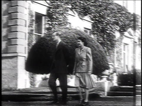 duke and duchess of edinburgh exiting broadlands front door / princess elizabeth and prince philip walking down steps outside castle / royal couple... - anno 1947 video stock e b–roll