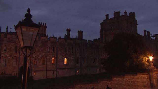 duke of edinburgh death: windsor castle night gvs; england: berkshire: windsor: windsor castle: ext / dusk various of windsor castle attendants... - differential focus stock videos & royalty-free footage
