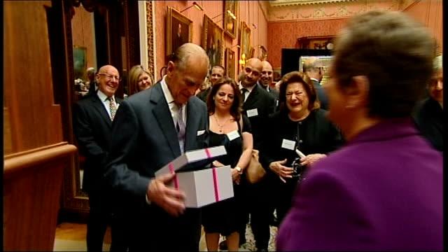 duke of edinburgh hosts rnid reception woman presents duke with birthday card duke looking at card woman presents duke with present of 'ear... - ohrenschützer stock-videos und b-roll-filmmaterial