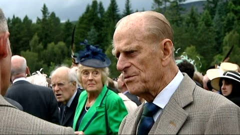 duke of edinburgh responding well to treatment for bladder infection; r07081201 balmoral castle: prince philip talking to people at garden party - blase harnapparat stock-videos und b-roll-filmmaterial