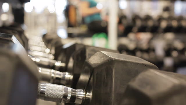 dumbbell at gym with people working out in the background - exercise equipment stock videos & royalty-free footage