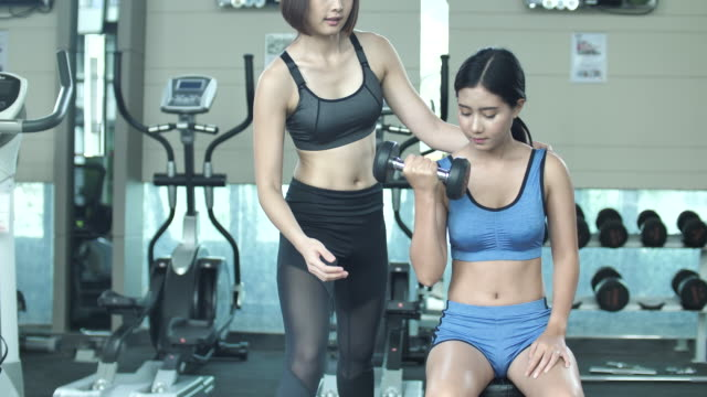 Dumbbells workout with personal trainer in gym