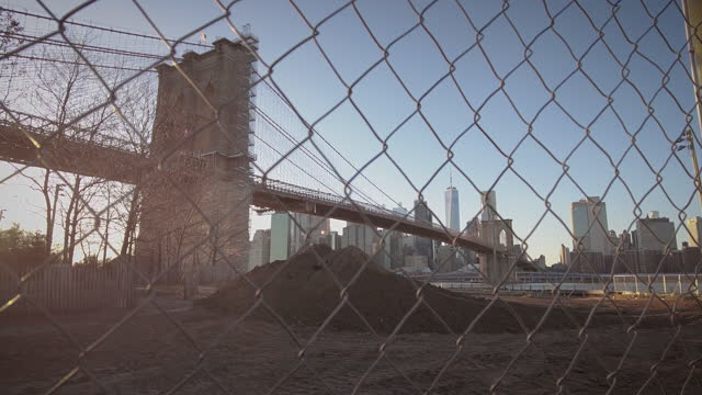 dumbo brooklyn empire fulton ferry park and brooklyn bridge. construction site renovations. fence in foreground. brooklyn bridge and manhattan... - focus on foreground stock videos & royalty-free footage