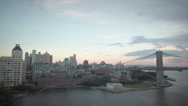 dumbo brooklyn view from the manhattan bridge with the brookyln bridge, the water front, brooklyn bridge park and the carousel. filmed during sunset... - skyline stock videos & royalty-free footage