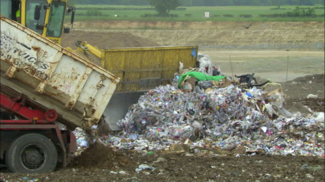 stockvideo's en b-roll-footage met ms, dump truck and bulldozer on landfill site, ardley, oxfordshire, united kingdom - afvalverwerking