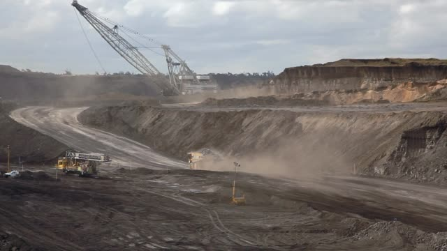 dump truck and dragline at open-pit coal mine - minatore video stock e b–roll