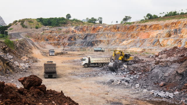 Dump truck being loaded with rock by shovel. Excavator operating in a rock quarry