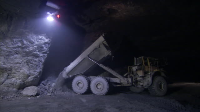 a dump truck deposits a load of ore under the glare of an overhead lamp in a mine. - metal ore stock videos & royalty-free footage