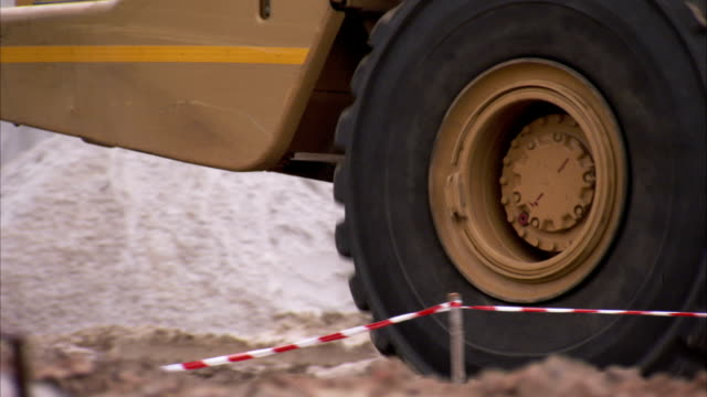 a dump truck drives over a construction site. available in hd. - dump truck stock videos & royalty-free footage