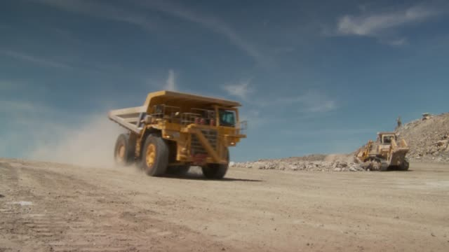 A dump truck drives through a dusty quarry. Available in HD.
