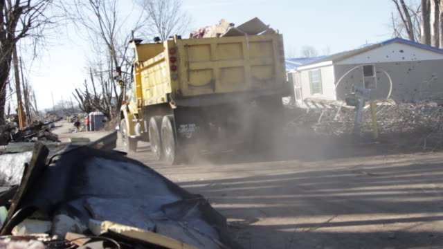 Dump Truck Driving By Destroyed Houses And Debris Piles