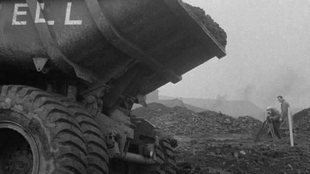 1954 b/w dump truck dumping dirt during performance trials / arkwright, england, united kingdom - 1954 bildbanksvideor och videomaterial från bakom kulisserna