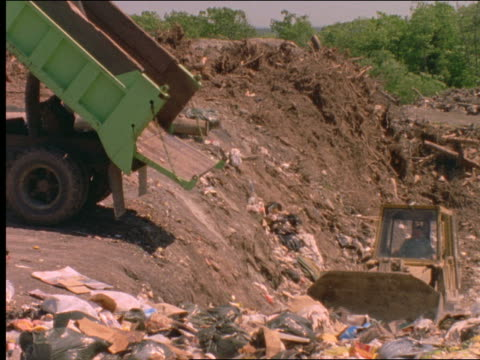 dump truck dumping garbage into landfill / bulldozer - dump truck stock videos and b-roll footage