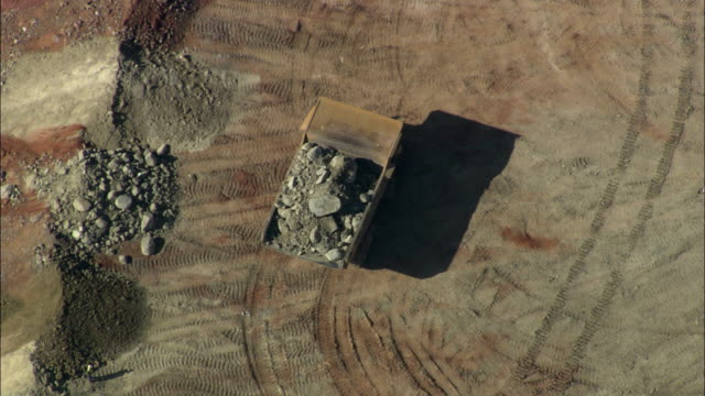 AERIAL WS ZO Dump truck dumping pile of rocks in quarry, Rustenburg, North West, South Africa