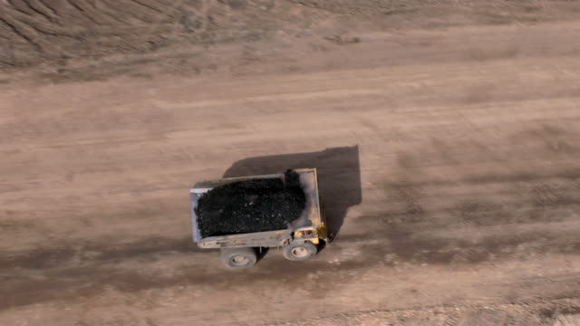 A dump truck full of coal drives through the Arizona desert.