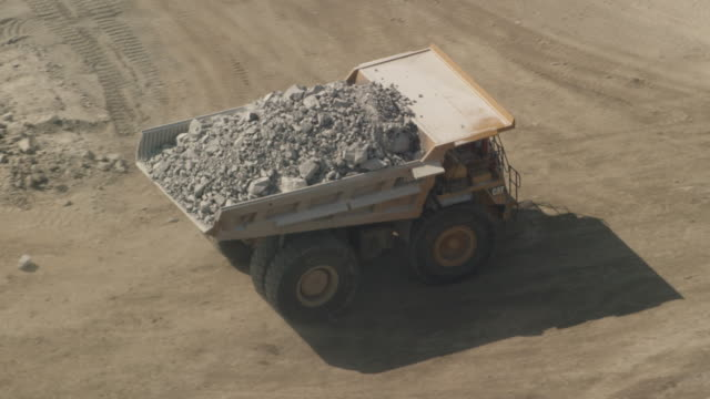 A dump truck removes rubble from an area on a mining site