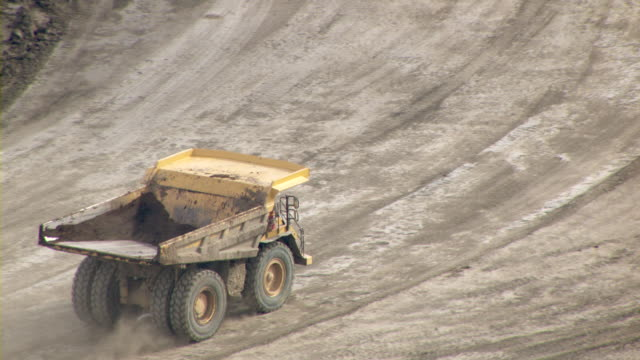 vídeos y material grabado en eventos de stock de a dump truck travels through an oil sands mine in fort mcmurray, canada. - camión de descarga