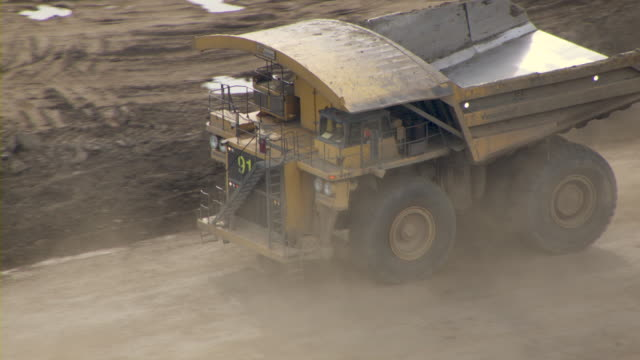 a dump truck travels through an oil sands mine in fort mcmurray, canada. - alberta stock videos & royalty-free footage