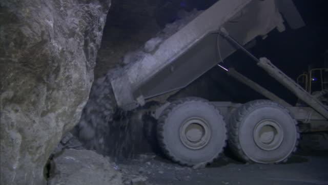 a dump truck unloads rocks in a mine shaft. - mining stock videos & royalty-free footage