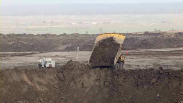 vídeos de stock e filmes b-roll de a dump truck unloads sand on the outskirts of an oil sands mine in fort mcmurray, canada. - camião basculante