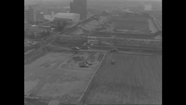 dump trucks and other heavy equipment operate at the redevelopment site near the yodobashi purification plant in postwar tokyo. - black and white点の映像素材/bロール